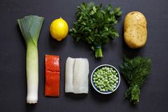 Fish pie ingredients on black background. Fish pie ingredients, leek, potato, salmon, haddock and herbs royalty free stock image