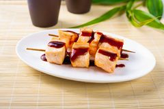 Fish pieces, grilled meat with dark sauce on a white plate. For menu stock photo