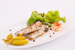 Fish on plate. Fish, peppers, lettuce  and cream on white plate Royalty Free Stock Photography
