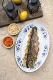 Fish plate in greek tavern. Roasted trout on onion. Stock Images