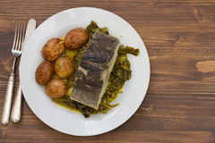 Fish with potato and vegetables on white plate and glass of water Royalty Free Stock Photos
