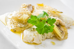 Fish with potatoes. Close up of fish with potatoes on white dish Stock Images