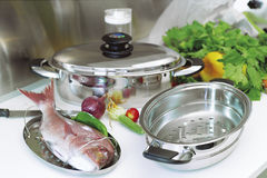 Fish and pots. Country Kitchen, preparing a meal with fish in stainless steel pot Stock Photos