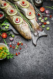 Fish Preparation with various ingredients for cooking on rustic background, top view Stock Photography