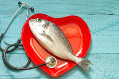 Fish on red heart plate and stethoscope Royalty Free Stock Images