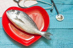 Fish on red heart plate and stethoscope Stock Image
