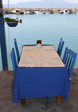 Fish Restaurant Lunch Setting with Blue Tablecloth and paper top by the Aegean Sea Royalty Free Stock Image