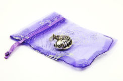 Fish Ring on Gift Bag. Silver fish ring on purple satin net mesh drawstring gift bag, isolated on white Stock Photography