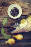 Fish a river pike perch on a wooden board with salt, bay leaf, onions, pepper. Stock Photography