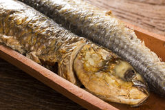 Fish roasted on the tile on old wood background Royalty Free Stock Image