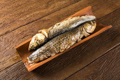 Fish roasted on the tile on old wood background Royalty Free Stock Photography