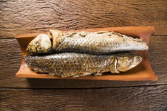 Fish roasted on the tile on old wood background Stock Photography