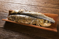 Fish roasted on the tile on old wood background Royalty Free Stock Photos