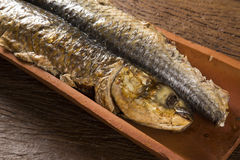 Fish roasted on the tile on old wood background Stock Images