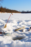 Fish and rod on the Ice close to hole while winter fishing Royalty Free Stock Photos