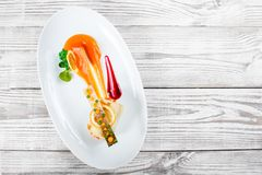 Fish rolls with vegetables, cheese and orange sauce on wooden background. Hot fish dish. Top view royalty free stock photos