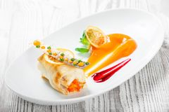 Fish rolls with vegetables, cheese and orange sauce on wooden background. Hot fish dish. Top view royalty free stock images