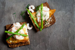 Fish on rye bread. A healthy Scandinavian lunch of fried, breaded plaice with prawns and asparagus on dark rye bread Stock Photography