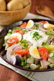 Fish salad with potatoes, eggs, red onion, tomatoes and dressing Stock Photos