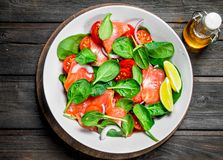Fish salad. Salad with slices of salmon, tomatoes and spinach with lime juice stock image