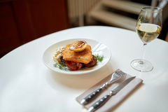 Fish salad and wine glass on restaurant table Stock Image