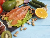 Fish salmon omega 3 avocado on blue wooden background healthy food stock photography