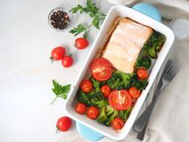 Fish salmon baked in oven with vegetables - broccoli, tomatoes. Healthy diet food, white marble backdrop, top view. stock photos