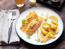 Fish salmon with crumple on top with baked potatoes and lemon slices. On a wooden background Royalty Free Stock Photo