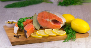 Fish salmon, lemon and greens placed on the table. Stock Images