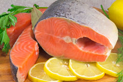 Fish salmon, lemon and greens placed on the table. Stock Image