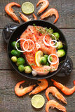 Fish salmon and shrimp with greens, lime and vegetables in a rustic style on wooden boards royalty free stock photography