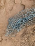 Fish on the sand, fishing equipment Green mesh on brown sand royalty free stock images
