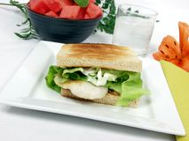 Fish sandwich. Exclusive fish fillet sandwich on square platter with decoration Stock Photos
