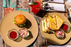Fish sandwich and burger. Delicious fresh fish sandwich, burger and green salad served for lunch Stock Images