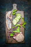Fish sandwich with herring and fresh healthy ingredients on dark cutting board. Top view Stock Images