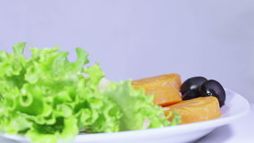 Fish sauce. On lettuce leaves stacked fish sauce poured framed carrots and olives stock video footage