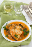 Fish in sauce on the plate and glass of wine Stock Image