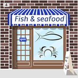 Fish and seafood shop. Fish and seafood shop building. Fish and crab sticker on window. Blue awnings. Brown brick facade. Advertising panel at the fore Royalty Free Stock Photo