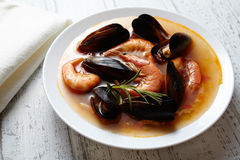 Fish seafood soup bouillabaisse. Mussels, shrimp, lobster in tomato sauce. White wooden background Stock Photo