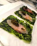 Fish on seaweed. A plate with fish fillets on bed of seaweed and fish eggs Royalty Free Stock Photo