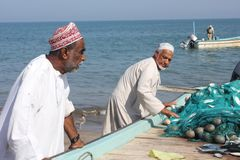 Fish seller in Barka, Oman. View of the Gulf of Oman (Indian Ocean) from Barka beach,  where fish seller are selling fish directly from the boat. It's amazing to Royalty Free Stock Photography