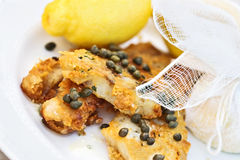 Fish Served With Lemons Tied in Cheesecloth. Fish in a buttery caper sauce served with lemons tied in cheesecloth Stock Images