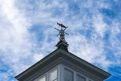 Fish shaped weather vane, against the blue sky, at an upward angle. Fish shaped weather vane against the blue sky, at an upward angle royalty free stock image