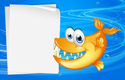 A fish with sharp teeth beside an empty paper under the water Royalty Free Stock Photos