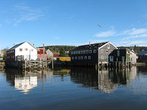 Fish sheds in the cove. Fishing sheds on stilts on the shore of the cove Stock Photo