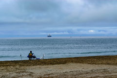 Fish and ships. Fisherman sits on shore while ships sail out to sea Royalty Free Stock Image