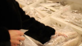 Fish shop. woman chooses frozen fish in the stock footage