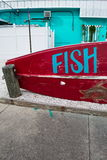 Fish sign on Red Boat. Fish sign written on red fishing boat outside of blue building on the coast of Florida in small town of Dunedin, Florida Stock Photos