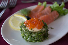 Fish snack with red caviar at restaurant. Stock Photography