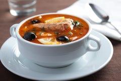 Fish solyanka. Solyanka, Russian soup with salmon, olives and lemon Stock Image